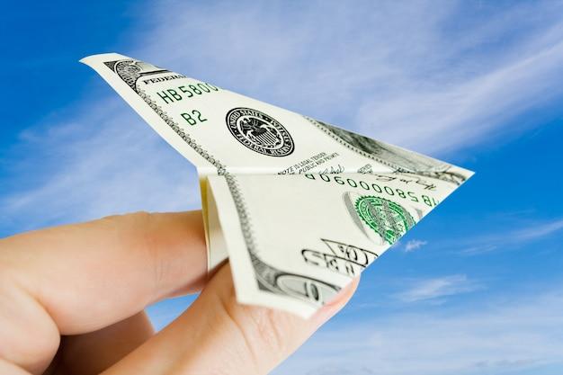 Avião do dinheiro nos dedos sobre o céu com nuvens