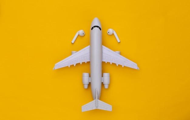 Avião e fones de ouvido sem fio em fundo amarelo.