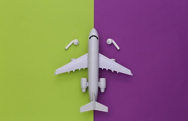 Avião e fones de ouvido sem fio em um fundo verde-púrpura.