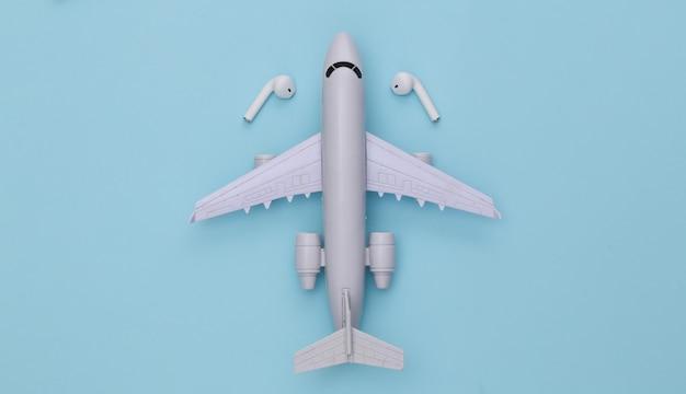 Avião e fones de ouvido sem fio sobre fundo azul.