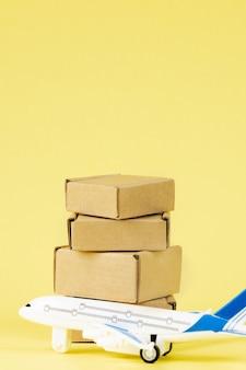 Avião e pilha de caixas de papelão. conceito de carga aérea e encomendas, correio aéreo. entrega rápida de mercadorias e produtos. aeronaves de carga. logística, conexão a locais de difícil acesso. banner, copie o espaço