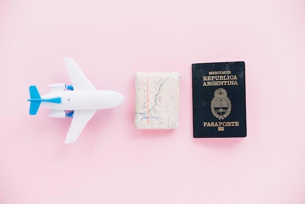 Avião em miniatura branco; mapa e passaporte em fundo rosa