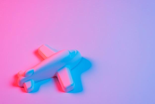 Avião em miniatura com luz azul no pano de fundo rosa