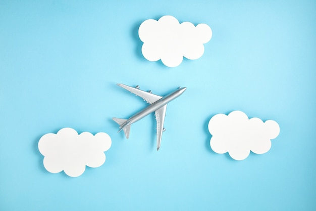 Avião em miniatura sobre uma parede azul com nuvens de papel. turismo de viagens, companhias aéreas, conceito de voos de baixo custo. vista superior, configuração plana.