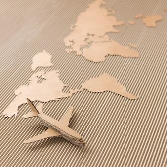 Avião em um mapa do mundo feito de papelão ondulado