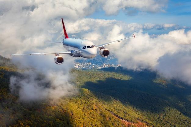Avião está voando nas nuvens sobre montanhas com floresta ao pôr do sol