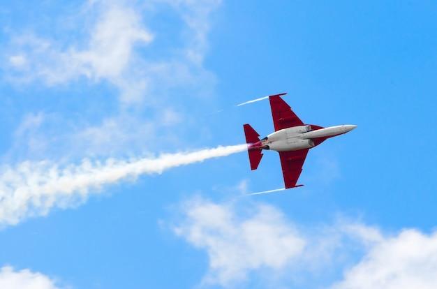 Avião lutador voa e fumaça céu azul.