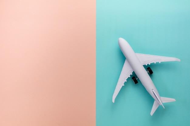 Avião modelo no fundo cor-de-rosa e azul da cor pastel.
