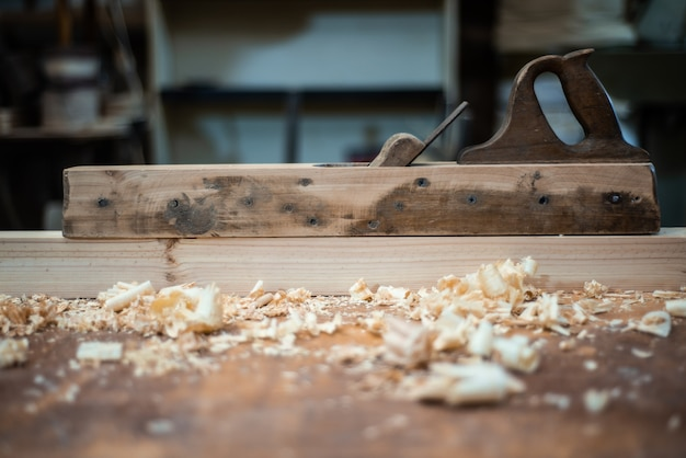 Avião na mesa do carpinteiro na oficina com serragem