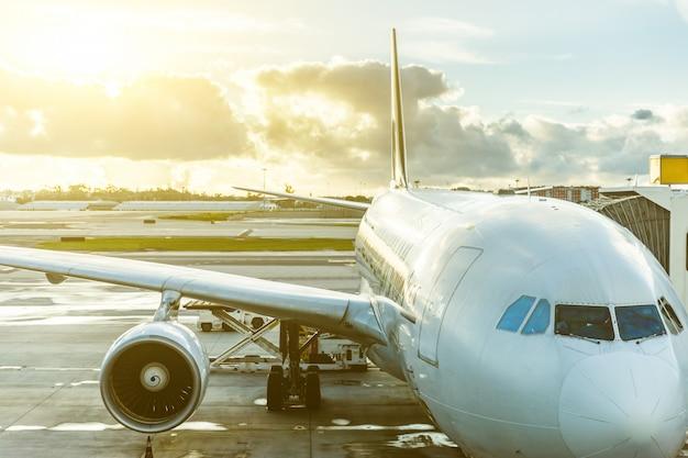 Avião no aeroporto close-up vista ao pôr do sol