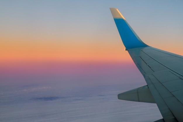 Avião no céu no nascer do sol que voa no das nuvens.
