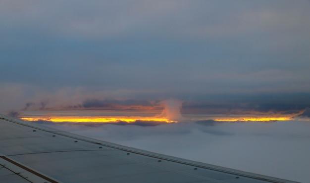 Avião no céu no nascer do sol voando na de nuvens.