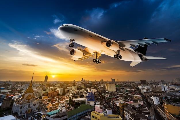 Avião para transporte sobrevoando a cidade no fundo do belo pôr do sol