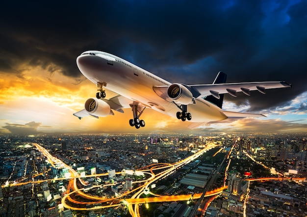 Avião para transporte voando sobre a paisagem urbana à noite na nuvem de tempestade na hora do pôr do sol