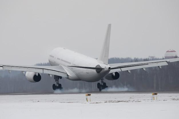 Avião pousando na pista com fumaça do chassi no inverno