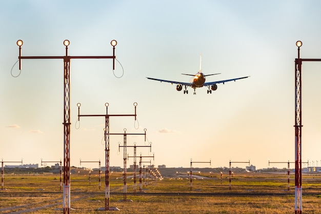 Avião pousando no pôr do sol, vista traseira com sistema de iluminação de aproximação