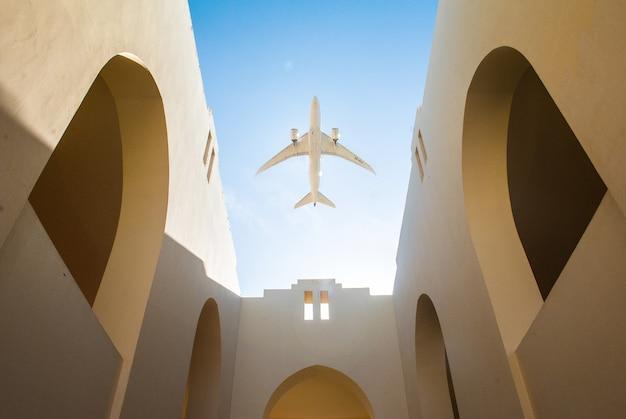 Avião sobre o pátio de estilo árabe da casa com paredes brancas e céu azul claro