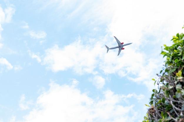 Avião voando a baixa altitude em um céu de nuvens e apuradas