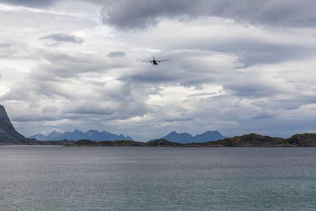 Avião voando no céu nublado dos fiordes noruegueses, lofoten