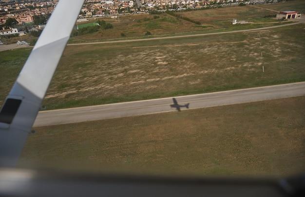 Avião voando sobre campos sob a luz do sol