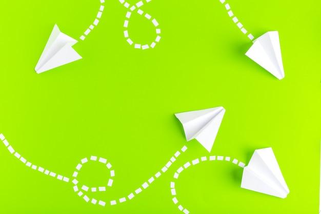 Aviões de papel conectados com linhas pontilhadas sobre fundo verde. conceito de negócios