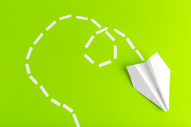 Aviões de papel conectados com linhas pontilhadas sobre fundo verde. o negócio