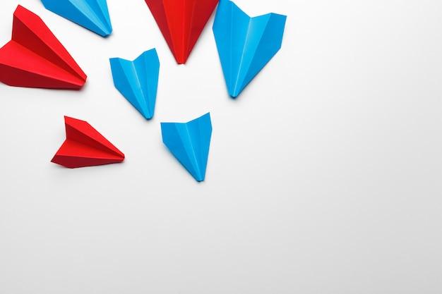 Aviões de papel vermelho e azul. conceitos de liderança e concorrência comercial