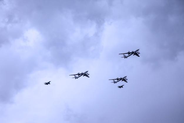 Aviões militares das forças armadas russas voam no céu com nuvens de textura. o avião está voando. desfile naval. dia da marinha na rússia. desfile naval. férias de são petersburgo, rússia. ensaio de desfile