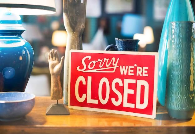 Aviso vermelho exibido entre artesanato de cerâmica em uma vitrine - desculpe, estamos fechados - para negócios em um conceito de comércio após o expediente ou bloqueio para a pandemia de covid-19