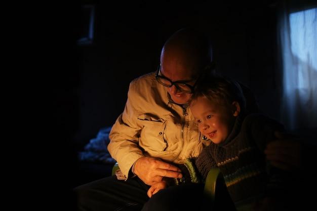 Avô abraça seu neto perto da lareira
