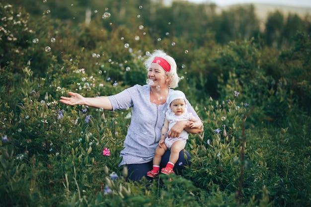 Avó, abraçando a neta na natureza em dia ensolarado de verão