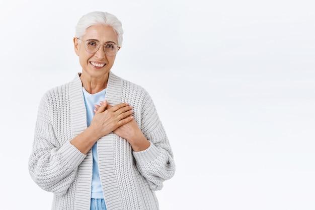 Avó adorável alegre, senhora idosa com cabelos grisalhos e rugas, parece tocada e encantada, toque o coração agradecida, sorrindo aprecia a surpresa de ano novo