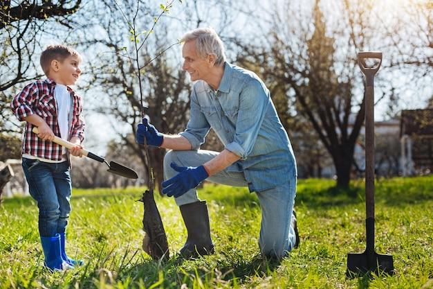Avô alegre ensinando seu netinho a cuidar da natureza plantando uma árvore no jardim da família
