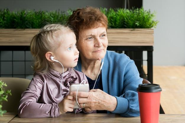 Avó aposentada e neta com um telefone em suas mãos.