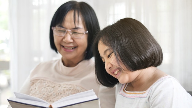 Avó asiática feliz e linda menina lendo livro juntos em casa
