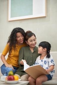 Avó asiática sorridente sentada no sofá com a filha e a neta adultas e lendo um livro com elas