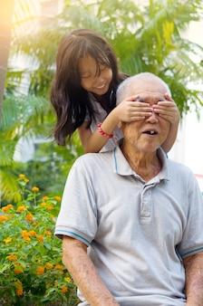 Avô asiático brincando com seus netos no parque