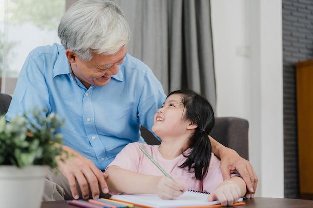 Avô asiático ensina neta desenho e fazendo lição de casa em casa. o chinês superior, vovô feliz relaxa com a moça que encontra-se no sofá no conceito da sala de visitas em casa.