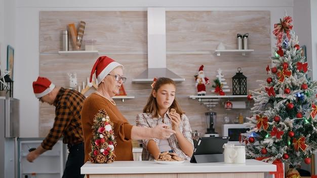 Avó assistindo vídeo de natal online com a neta no tablet enquanto o avô trazendo leite