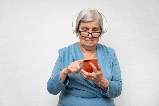Avó avançada ouvindo áudio em fones de ouvido usando o smartphone.