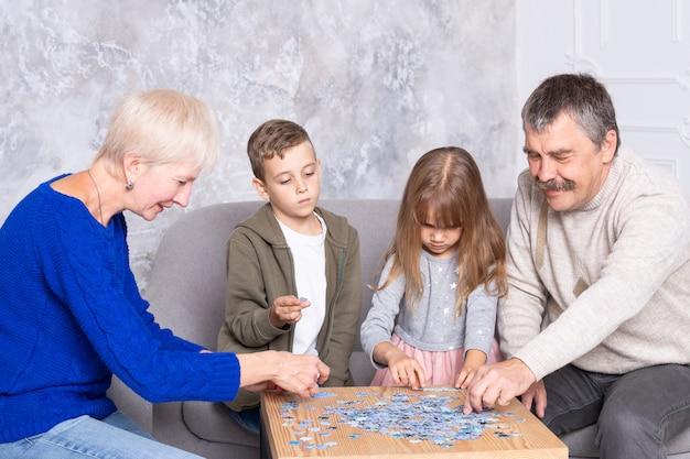 Avó, avô e neta colecionam quebra-cabeças à mesa na sala de estar. a família passa tempo juntos, jogando