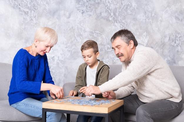 Avó, avô e neto colecionam quebra-cabeças à mesa na sala de estar. a família passa tempo juntos, jogando jogos educativos