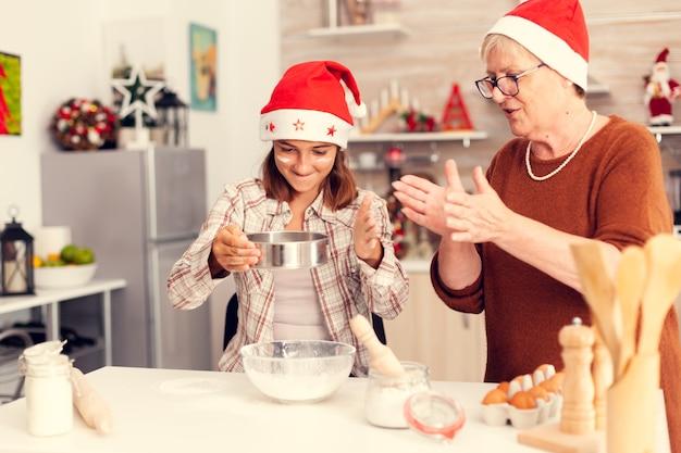 Avó batendo palmas no dia de natal e sobrinha fazendo massa