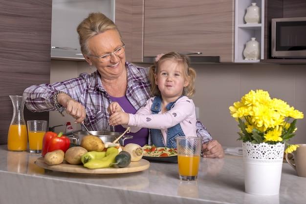 Avó brincando com a neta na cozinha