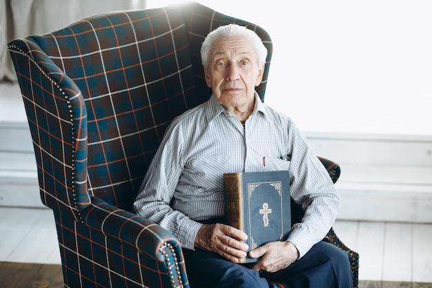 Avô com a bíblia se senta em uma cadeira