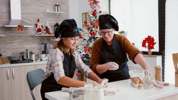 Avó com a neta de avental de cozinha preparando a tradicional massa caseira