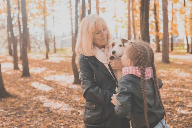 Avó com a neta no outono parque, garota abraçando a avó e seu jack russell terrier