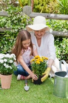 Avó com a neta trabalhando no jardim