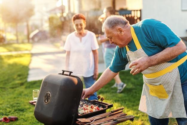 Avô com avental, verificando na grelha e segurando o copo de cerveja em pé no quintal.