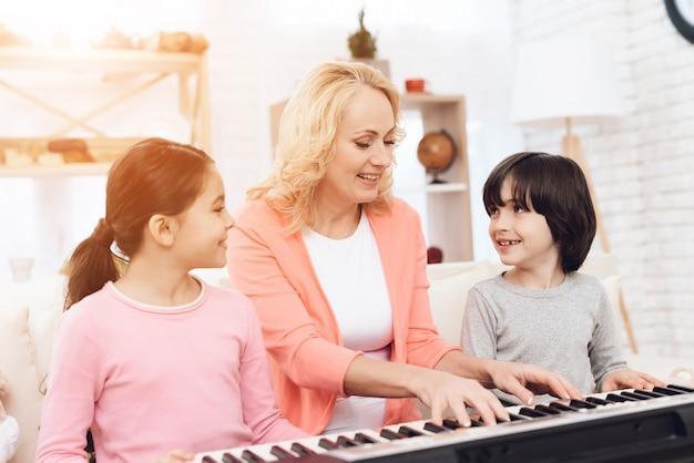 Avó com crianças ensinando a tocar piano em casa
